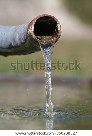 Crystal clear fresh water emerging from a rusty pipe. Conceptual image illustrating water scarcity and the importance of fresh clean water in the environment. - stock photo