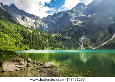 Crystal clear mountain lake and rocky mountains - stock photo