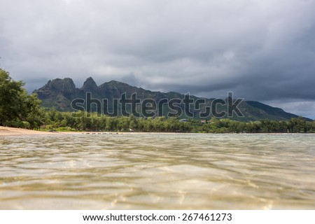 Crystal clear sparkling water on a beach on Kauai with Nounou Mountain (Sleeping Giant) in the background with a storm cloud over it - stock photo