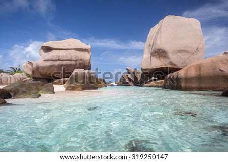 Crystal Clear Waters Of Anse Marron Overlooked By Two Huge Granite Boulders - stock photo