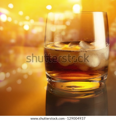 crystal glass with whiskey on a glass table - stock photo