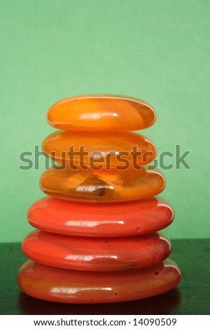 Crystal orange pebbles in balance with green background - stock photo