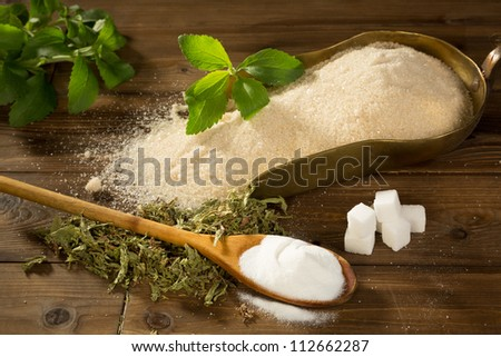 Crystal sugar and lumps together with powder and dried stevia natural sweetener on a wooden table - stock photo