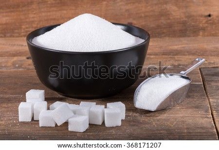 Crystal sugar and sugar cubes, on wooden background - stock photo