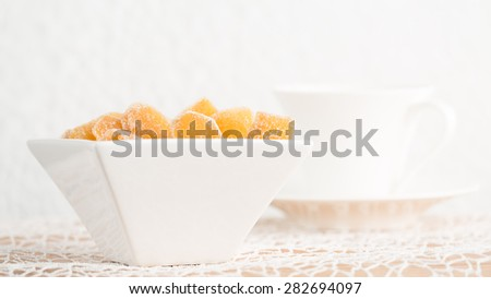 Crystallized ginger root  in white porcelain bowl and cup of tea on the background. Shallow DOF. Close-up photo, horizontal - stock photo