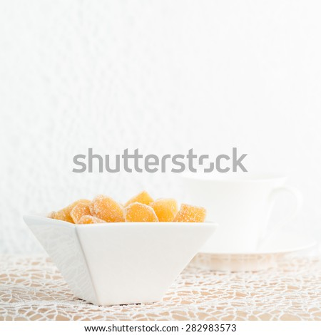 Crystallized ginger root  in white porcelain bowl and cup of tea on the background. Shallow DOF, square - stock photo