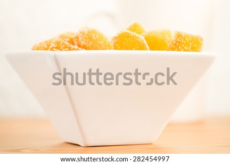 Crystallized ginger root  in white porcelain bowl. Shallow DOF. Close-up photo, horizontal, warm tone - stock photo