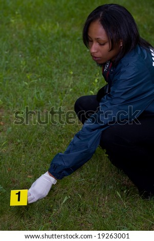 CSI places a numbered marker near evidence - stock photo