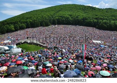 CSIKSOMLYO, ROMANIA - JUNE 7: Crowds of Hungarian pilgrims gather to celebrate the Pentecost and the catholic pilgrimage on June 7, 2014 in Sumuleu Ciuc (Csiksomlyo), Romania - stock photo