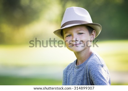 cuacasian boy smiling wearing a hat in the park - stock photo