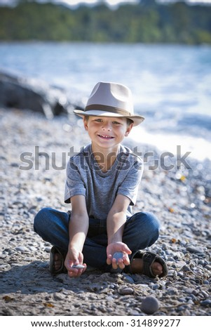 cuacasian boy smiling wearing a hat on the beach - stock photo
