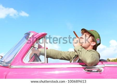 Cuba concept. Vintage car with cigar smoking man with Fidel Castro patrol cap. Funny image cuban conceptual image. - stock photo
