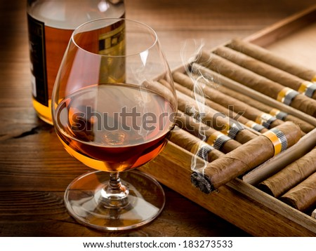 cuban cigar and bottle of cognac on wood background - stock photo