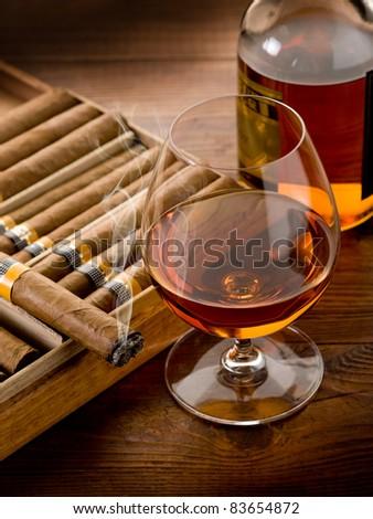 Cuban cigar and bottle of liquor on wood background - stock photo