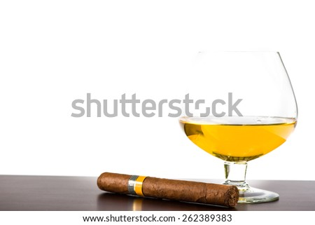 Cuban cigar and glass with rum or cognac isolated on wooden bar - stock photo