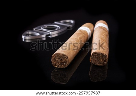 Cuban cigars on a black background with a cigarette cutter  - stock photo