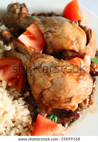 Cuban style chicken in tomato and black bean sauce, served with brown rice. - stock photo