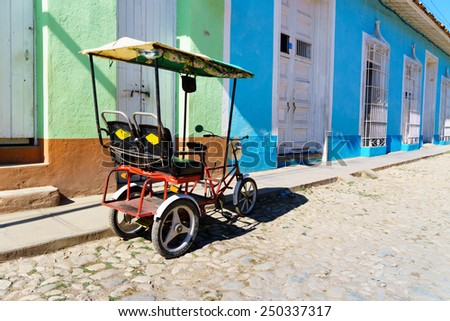 Cuban taxi bicycle parked in front of colorful colonial houses on Trinidad street  - stock photo