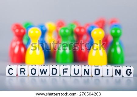 Cube Letters show crowdfunding  in front of unsharp ludo figures. Background is light gray - stock photo