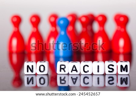 Cube Letters show no racism in front of colorful unsharp ludo figures. - stock photo