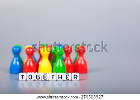 Cube Letters show together  in front of unsharp ludo figures. Background is light gray - stock photo