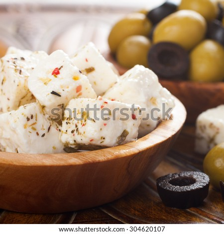 Cubed feta cheese in olive wood bowl and green and black olives on rustic wooden background.  Selective focus. - stock photo