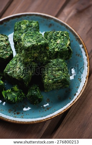 Cubes of chopped and compressed spinach, selective focus - stock photo