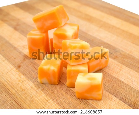 Cubes of Colby Cheese isolated on wooden board - stock photo