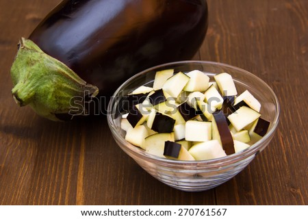Cubes of eggplant on bowl on wooden table - stock photo