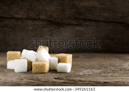 Cubes of sugar cane brown and white refined over wooden background with copy space - stock photo