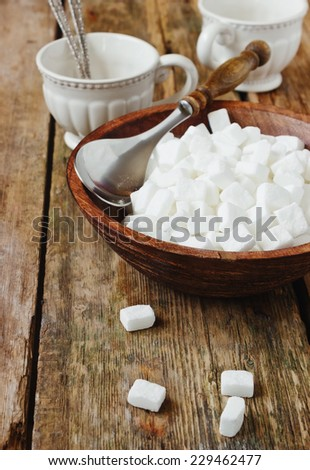 cubes of white sugar in a wooden bowl on old wooden table - stock photo
