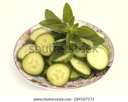 cucumber and oregano on a plate - stock photo