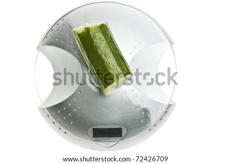 Cucumber isolated on food scale - stock photo