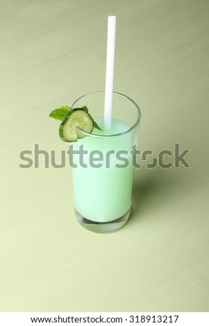 cucumber juice on light green background - stock photo