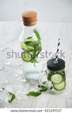 Cucumber mint drink Fresh summer homemade lemonade to cool down with mineral water and ice. Rustic jar with straw and closed vintage bottle with beverage, top view - stock photo