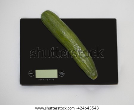 Cucumber on a digital white kitchen scale. (weighing products) - stock photo