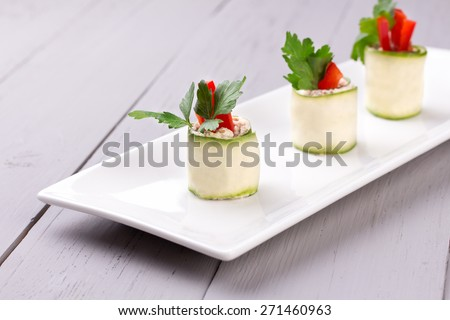 Cucumber rolls on white plate - stock photo