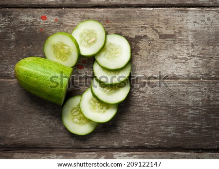 cucumber slices on wooden background - stock photo