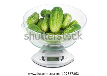 Cucumbers are weighed in the balance isolated on a white background horizontal - stock photo