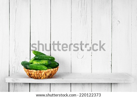 Cucumbers in a basket on a wooden shelf. - stock photo