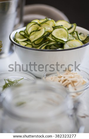 Cucumbers in a bowl, sliced to be pickled. - stock photo