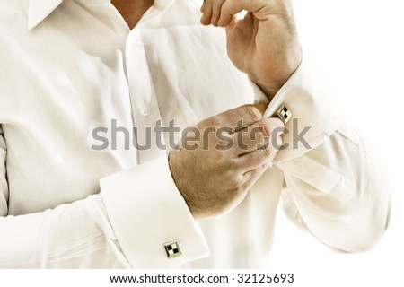 Cuff with cufflink being put on - stock photo