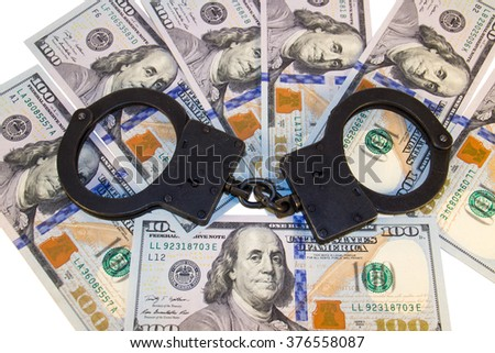 cuffs on the background of hundred dollar bills - stock photo