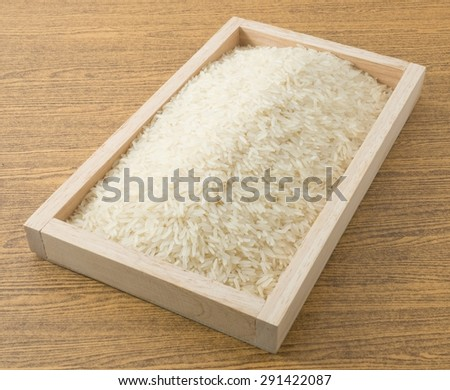 Cuisine and Food, Uncooked White Long Rice, Basmati Rice or Thai Jasmine Rice in A Wooden Tray. - stock photo