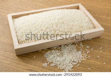 Cuisine and Food, White Long Rice, Basmati Rice or Jasmine Rice in A Brown Wooden Tray. - stock photo