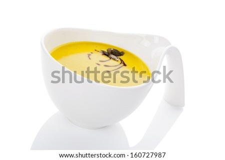 Culinary delicious hokkaido pumpkin soup in white bowl isolated on white background with reflection. Healthy seasonal autumn eating.  - stock photo