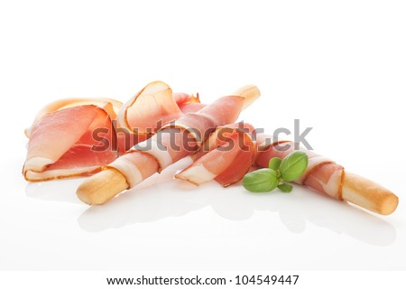 Culinary food. Parma ham prosciutto with grissini bread sticks isolated on white background. - stock photo