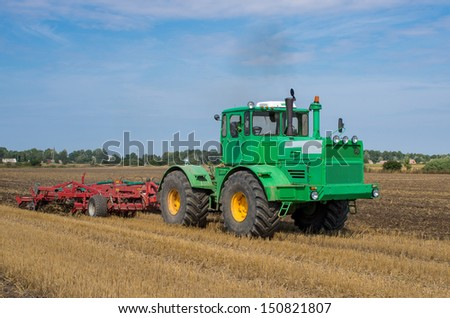 Cultivating tractor in the field. Lithuania country. - stock photo