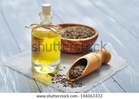 cumin oil in a glass bottle with cumin seeds on wooden background - stock photo