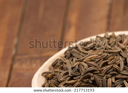 cumin seeds in wooden spoon - stock photo